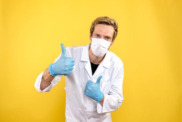 Вид спереди мужской доктор улыбается в маске на желтом фоне пандемический медик covid- Бесплатные Фотографии