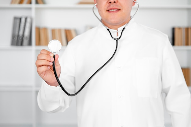 Front view male doctor using a stethoscope Free Photo