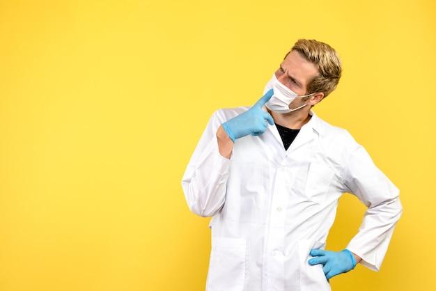 Vista frontale medico maschio su sfondo giallo salute medico pandemia covid Foto Gratuite