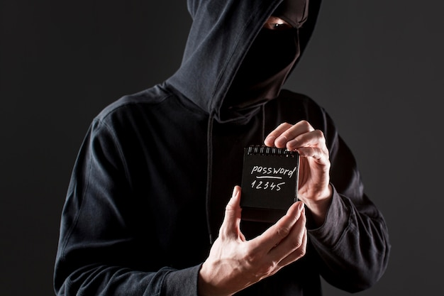 Front view of male hacker holding notebook with password Free Photo