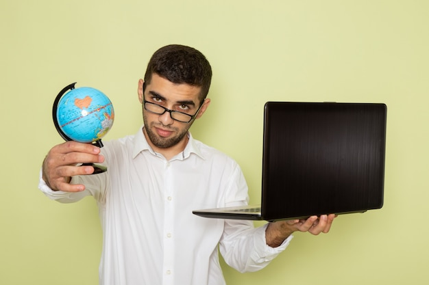Front view of male office worker in white shirt holding his laptop and globe on the green wall Free Photo