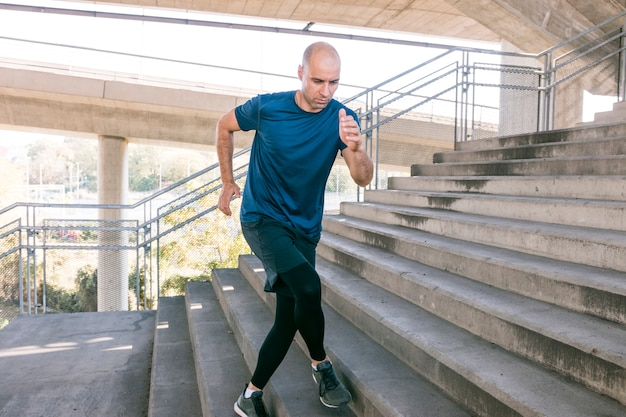 Front view of male runner sportsman running up city stairs jogging