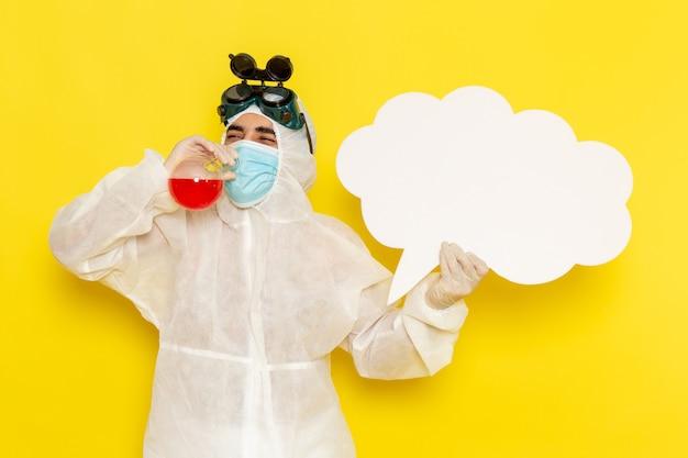 Вид спереди научный работник-мужчина в специальном защитном костюме, держащий фляжку с красным раствором, большой белый знак на желтом столе Бесплатные Фотографии