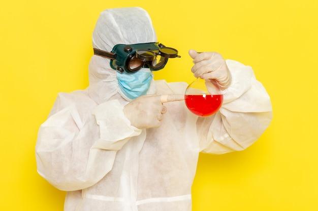 Вид спереди научный сотрудник мужского пола в специальном защитном костюме, держащий колбу с красным раствором на желтой поверхности Бесплатные Фотографии