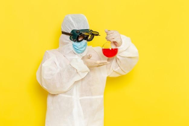 Вид спереди научный сотрудник-мужчина в специальном защитном костюме, держащий фляжку с красным раствором на желтом столе Бесплатные Фотографии