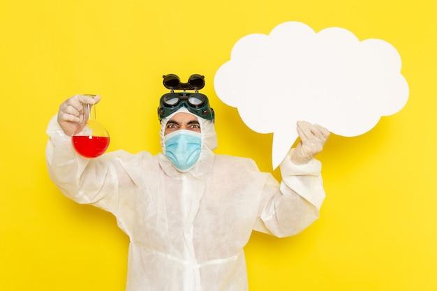 Operaio scientifico maschio vista frontale in vestito protettivo speciale che tiene boccetta con soluzione rossa grande segno bianco sullo scrittorio giallo Foto Gratuite