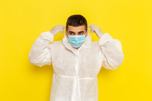 Vista frontale del lavoratore scientifico maschio in tuta protettiva speciale che indossa la sua maschera sulla parete gialla Foto Gratuite