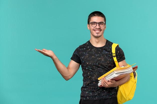 Vista frontale dell'allievo maschio nello zaino giallo della maglietta scura che tiene file e libri sorridenti sulla parete azzurra Foto Gratuite