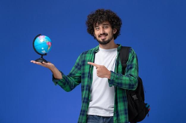 Vista frontale dello studente maschio in camicia a scacchi verde che porta zaino nero e che tiene piccolo globo che sorride sulla parete blu Foto Gratuite