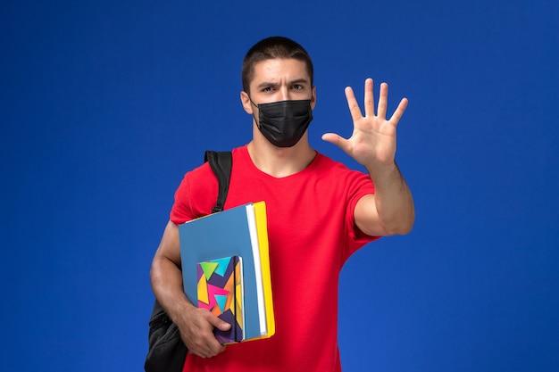 青い机の上にコピーブックとファイルを保持している黒い滅菌マスクのバックパックを身に着けている赤いtシャツの正面図の男子生徒。 無料写真