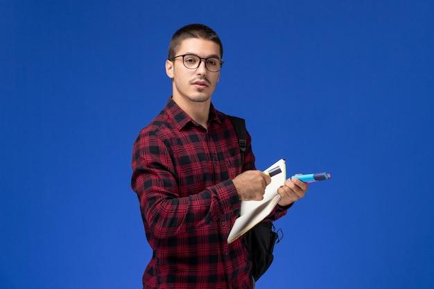Vista frontale di uno studente maschio in camicia a scacchi rossa con zaino che tiene il quaderno di pennarelli sulla parete blu chiaro Foto Gratuite