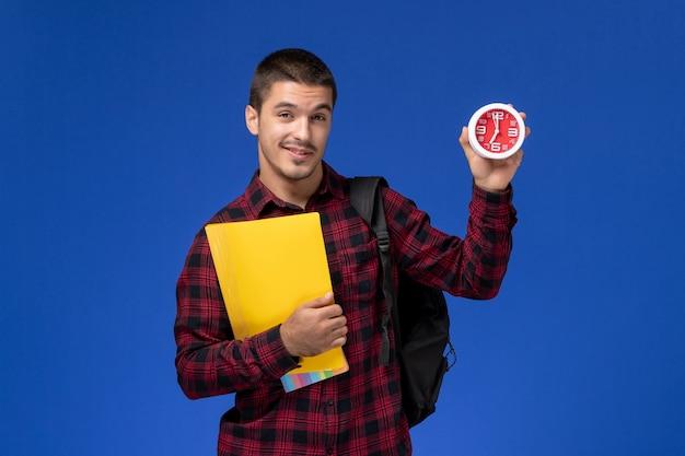 Vista frontale dello studente maschio in camicia a scacchi rossa con zaino che tiene file gialli e orologi sulla parete blu Foto Gratuite