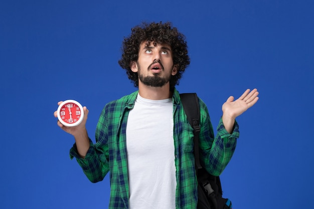 Front view of male student wearing black backpack holding clocks on light blue wall Free Photo