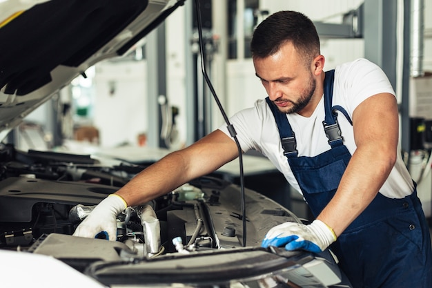 Front view male worker in car service shop Free Photo