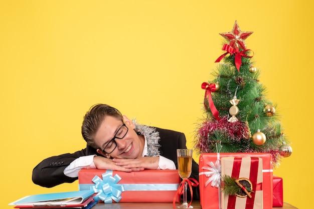 クリスマスプレゼントと一緒に座っている正面図の男性労働者 無料写真