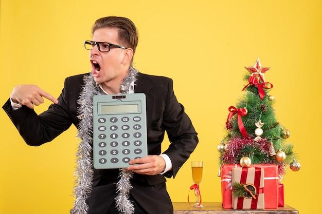 Lavoratore di sesso maschile vista frontale in tuta in piedi e con rabbia tenendo calcolatrice Foto Gratuite