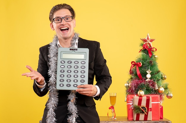 Front view male worker in suit standing and holding calculator Free Photo