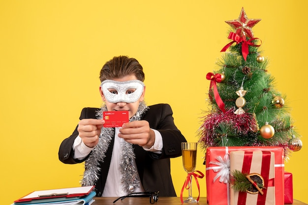 Vista frontale lavoratore di sesso maschile che indossa la maschera del partito e tenendo la carta di credito Foto Gratuite