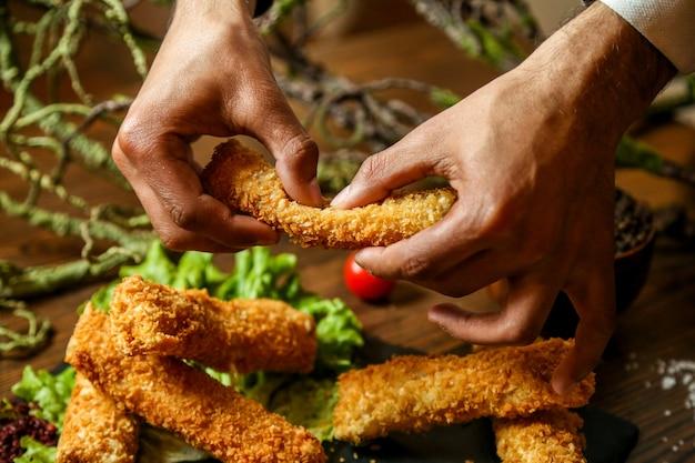 Мужчина вид спереди ломает куриные наггетсы с соусами на подставке Бесплатные Фотографии