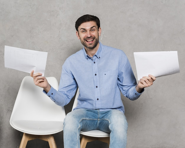 Front view of man on chair holding resumes for employment Premium Photo