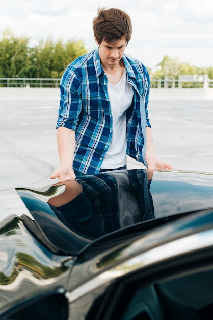 Front view of man closing car hood Free Photo
