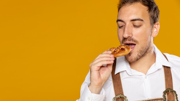 Front view of man eating german pretzel Free Photo