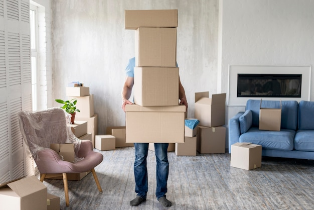 Front view of man holding boxes while moving out covering his face Free Photo