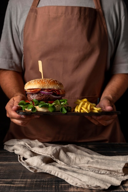 Front view man holding tray with burger and fries Free Photo