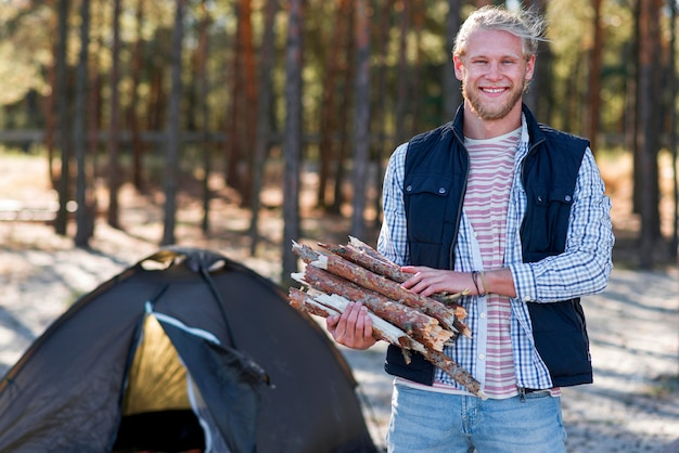 Uomo di vista frontale che tiene legno per il fuoco Foto Gratuite