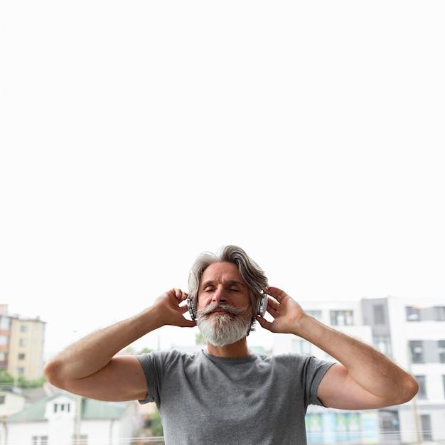 Vista frontale uomo che ascolta la musica Foto Gratuite