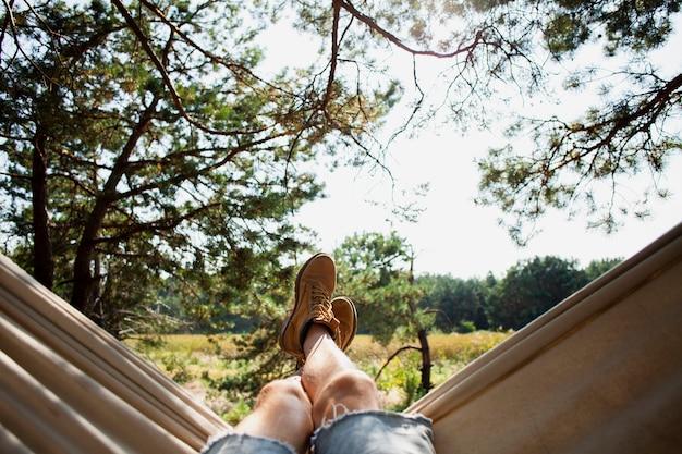 Вид спереди человек в гамаке расслабляющий Premium Фотографии