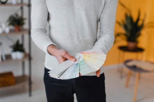 Vista frontale dell'uomo che intende ridipingere la casa usando la tavolozza della vernice Foto Gratuite