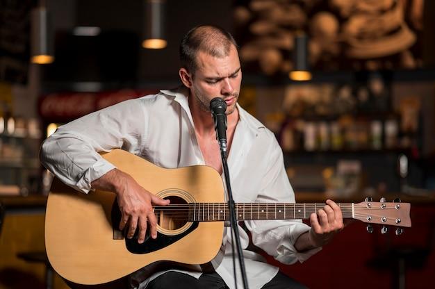 正面男がバーでギターを弾く 無料写真