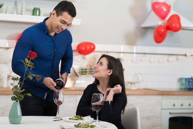 Front view man pouring wine in a glass for his wife Free Photo