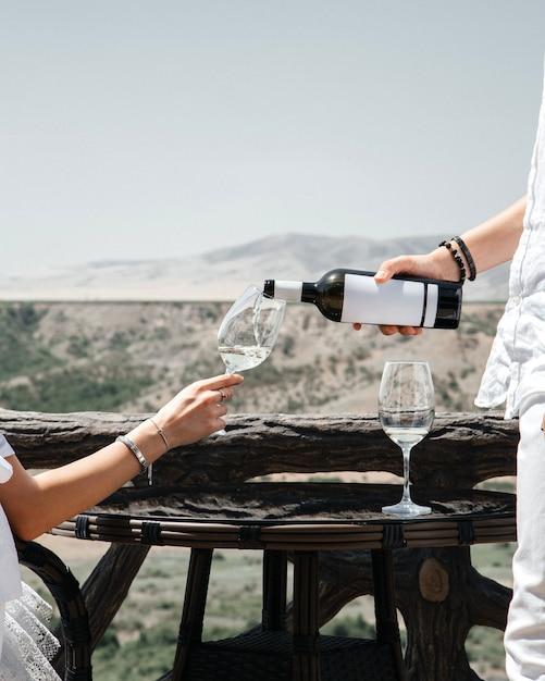 Un uomo di vista frontale che versa il vino nel vetro delle femmine sul vino della gente umana dell'alcool di vista della città Foto Gratuite