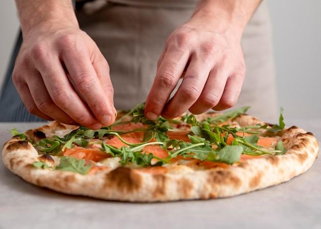 Вид спереди мужчина кладет рукколу на тесто для запеченной пиццы с ломтиками копченого лосося Бесплатные Фотографии