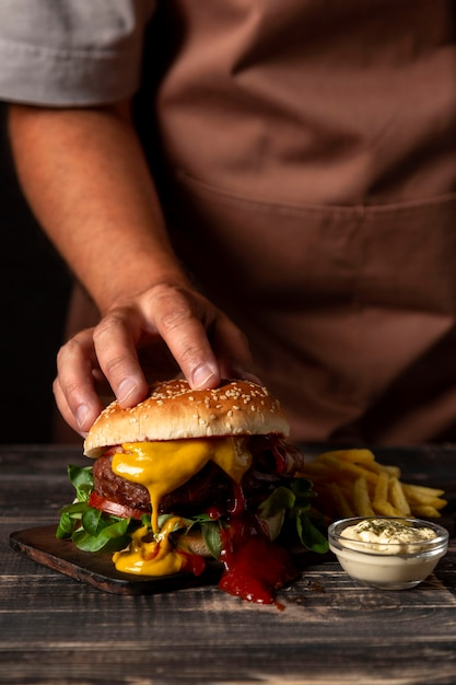 Front view man putting hand on burger Premium Photo
