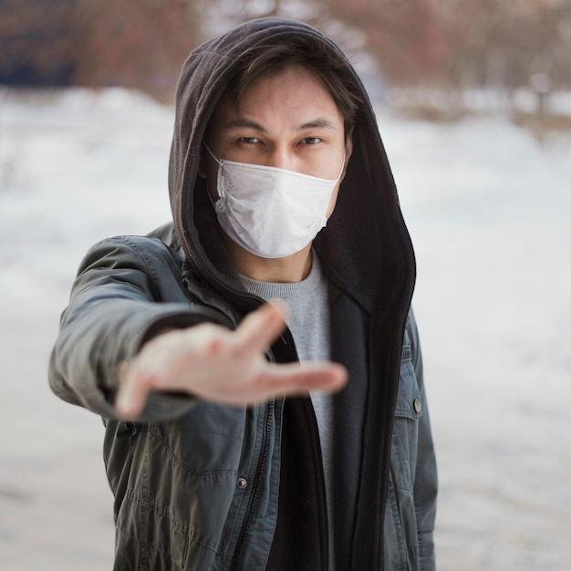 Front view of man reaching for someone while wearing a medical mask Free Photo