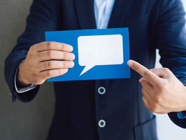 Front view man showing a card with a speech bubble mock-up Premium Photo