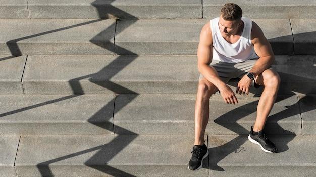 コピースペースと階段に座っている正面図男 無料写真