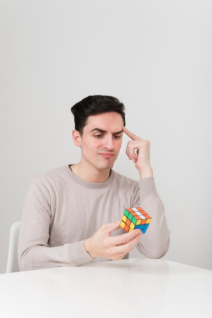 Front view man solving rubiks cubs Free Photo