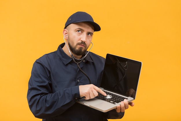 Front view man troubleshooting a laptop Free Photo