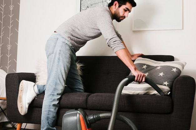 Front view man vacuuming couch Free Photo