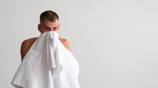 Front view of man wiping his face with towel after washing Free Photo