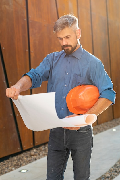 Front view of man with blueprint Free Photo