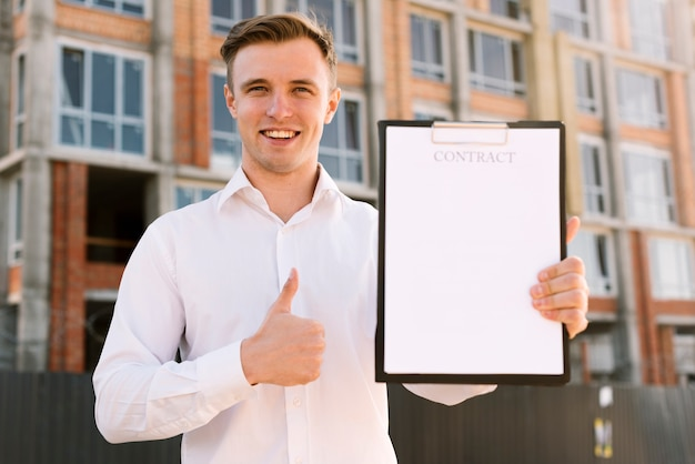 Front view man with contract showing approval Free Photo