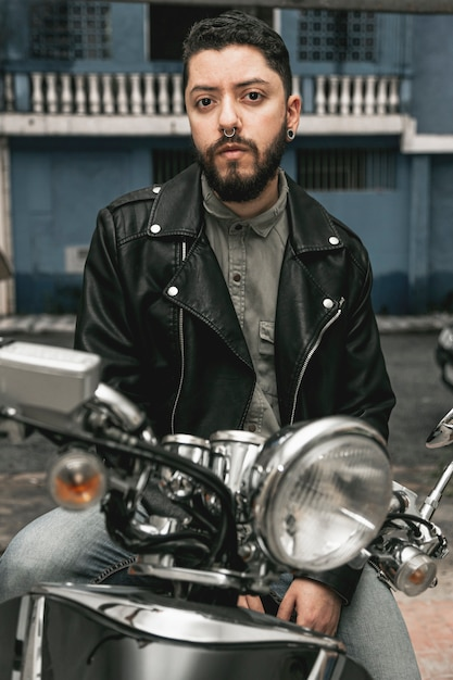 Front view man with leather jacket on motorcycle Free Photo