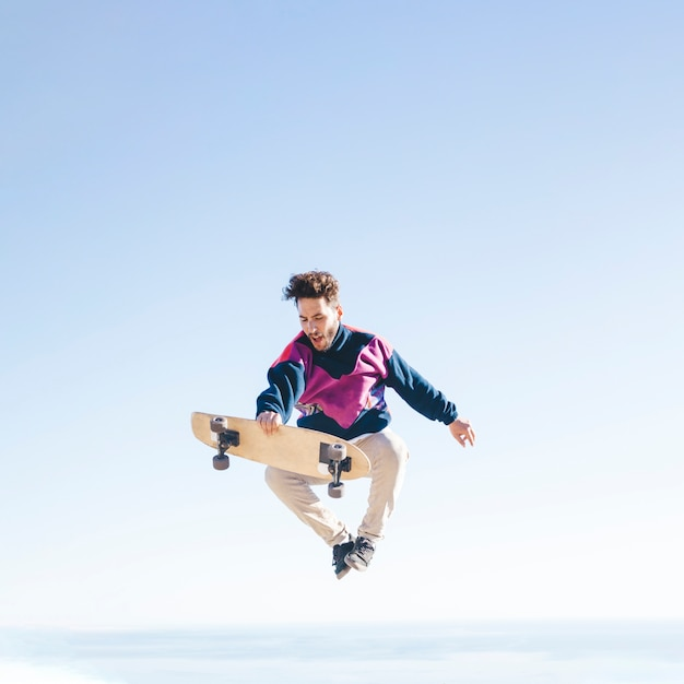 Front view of man with skateboard in air Free Photo