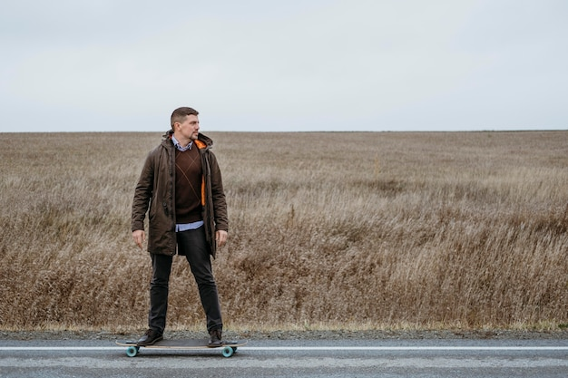 Front view of man with skateboard on the road Free Photo