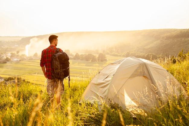 Вид спереди человек с палаткой Premium Фотографии